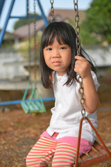 Asian child siting swing at playground