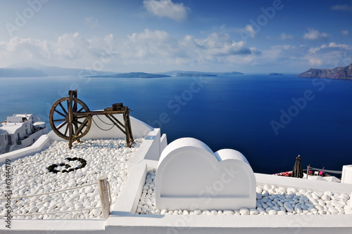 Old water pump wheel on rooftop with Aegean Sea in background, O