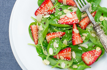 Spinach and strawberry salad closeup, top view