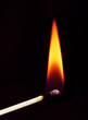 burning matchstick on black background