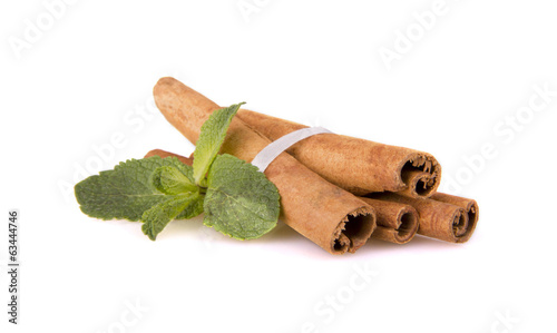 cinnamon sticks and mint leaf on a white background