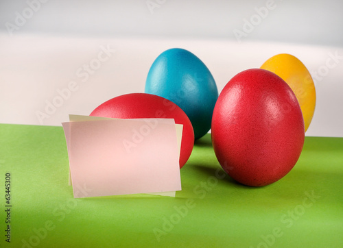 Colorful Easter eggs and blank editable paper notes.