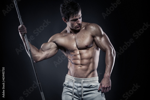 Muscular bodybuilder guy doing posing with dumbbells over black
