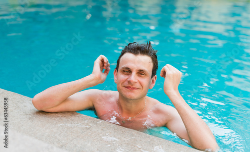 Young wet sexy man posing in the swimming pool