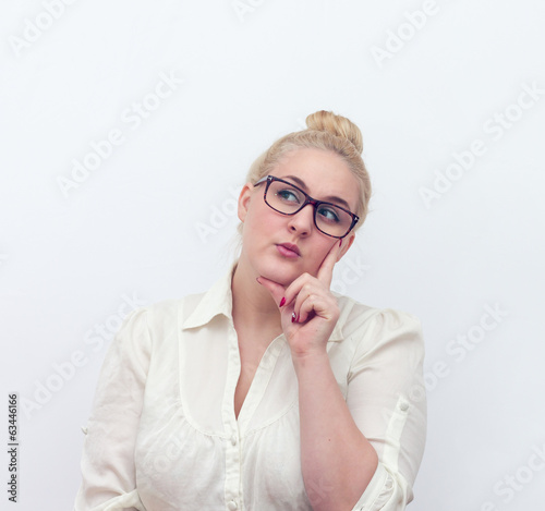 Doubtful young woman thinking, on white