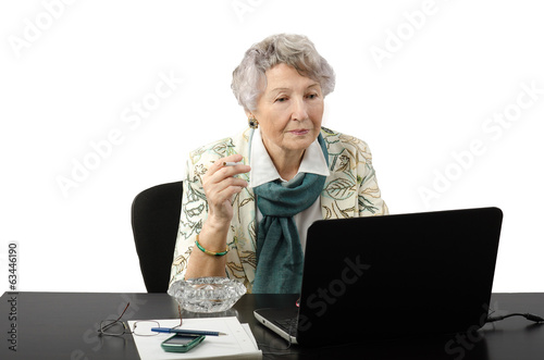 Grey haired business woman stares at the laptop screen