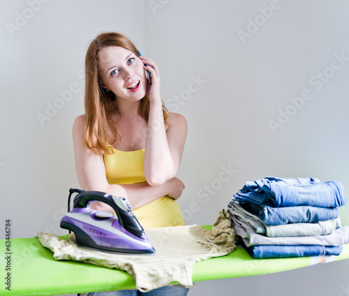 Housewife talking on the phone while ironing on grey background