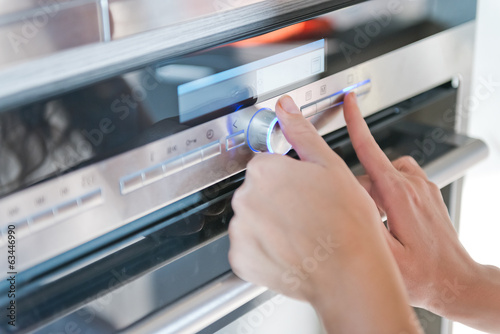 Hand moving the timer knob on the oven
