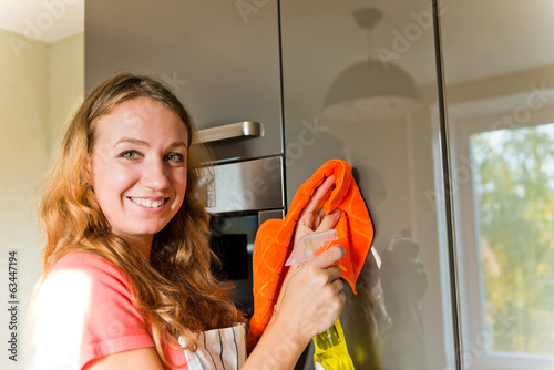 girl wiping the dust from wooden furniture at home