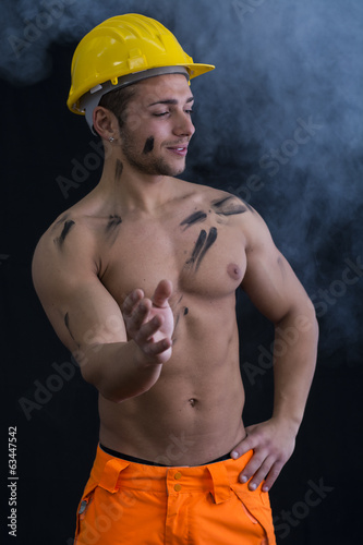 Muscular young construction worker shirtless with smoke around