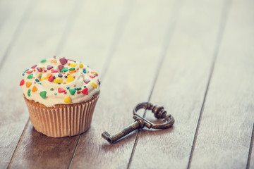 Cupcake and key on wooden table.
