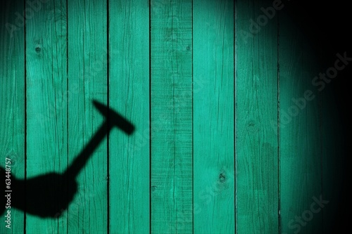 Shadow of a hand with hammer on natural wooden background