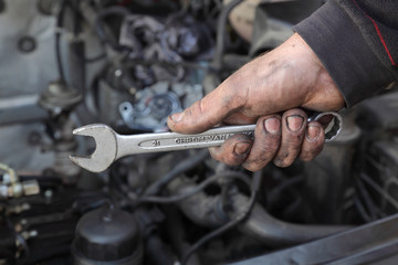 Car mechanic hold spanner tool in hand