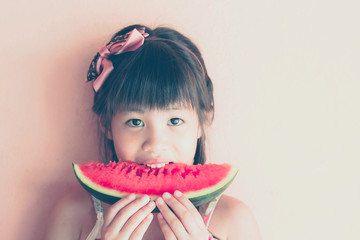 cute little asian girl eating watermelon