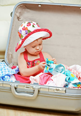 happy baby girl is going on trip, pack suitcase