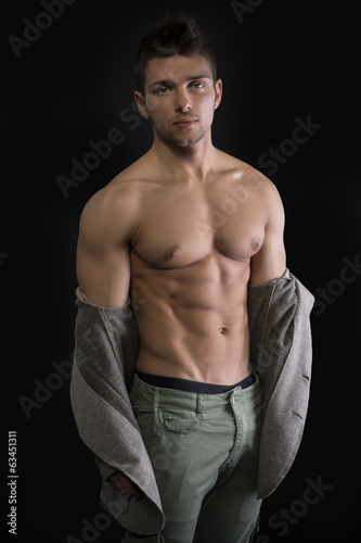 Young muscular man with jacket pulled down on naked torso
