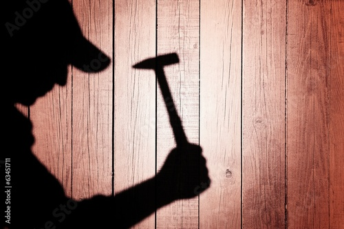 Shadow of a man with hammer on natural wooden background