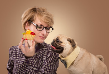 Pretty woman stopping her dog from eating cake