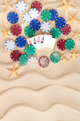 Four aces with poker chips on beach sand