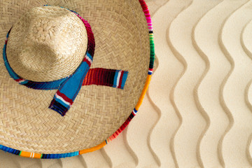 Straw sombrero on golden wavy beach sand