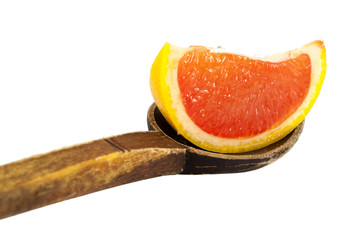 Red grapefruit slice into a wooden spoon