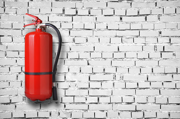 fire extinguisher on white brick wall