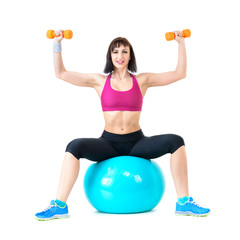 Young woman exercising with dumbbells on a fitness ball