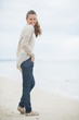 Full length portrait of happy young woman on cold beach