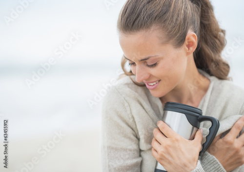 Portrait of woman sitting on beach with cup of beverage
