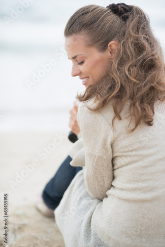 Happy woman sitting on cold beach. rear view