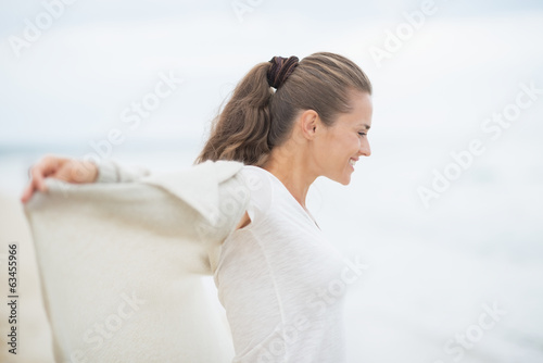 canvas print picture Happy young woman on cold beach rejoicing