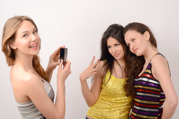 Blonde woman photographing, smiling a couple of brunette women