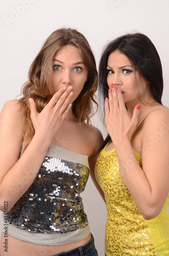 Two women holding their hands on their mouths surprised