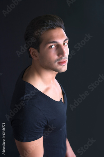 Brown eyed, black haired latin man on dark background
