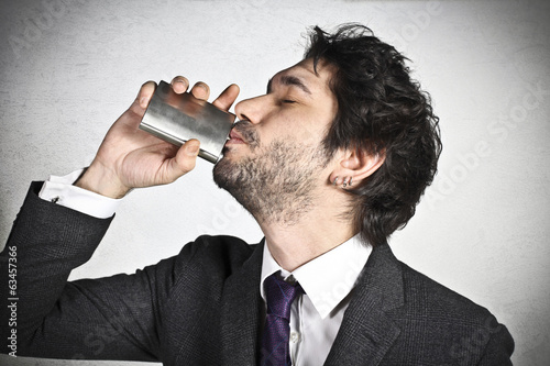 Young businessman drinks alcohol
