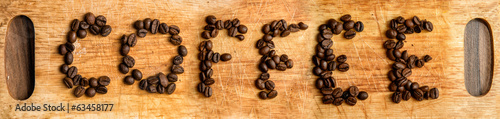 Inscriprion of coffee grains on wooden background