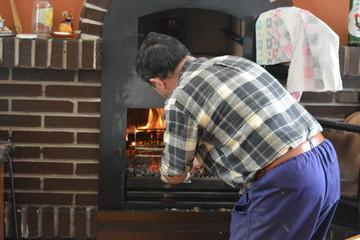 Hombre metiendo parrilla en el horno