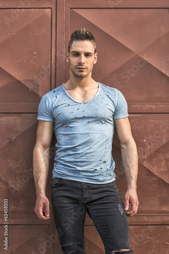 Young man standing against red metal doors