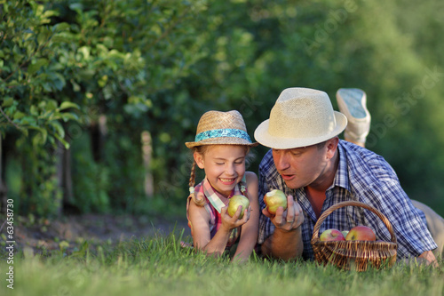 dad and daughter in the garden eating apples