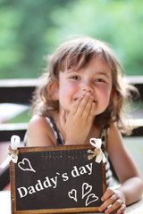 smiling little girl holding a gift for the father