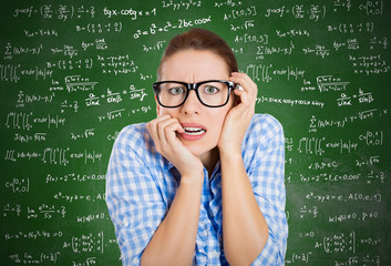 Anxious student in front of chalkboard filled with math formulas