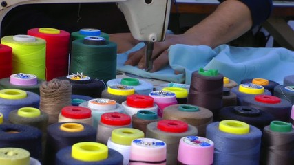 Tailor with the sewing Machine and colorful Bobbins