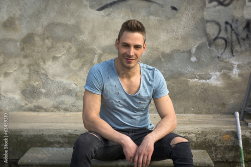 Smiling young man sitting on concrete steps