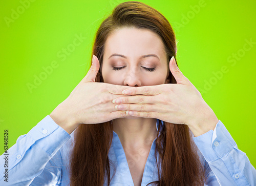 Woman covering her mouth, eyes closed speak no evil concept