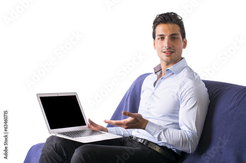 Young man showing laptop computer sitting on couch.