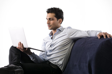 Young man working on laptop computer while sitting on couch.