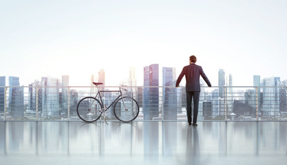 Businessman with bicycle looks at city