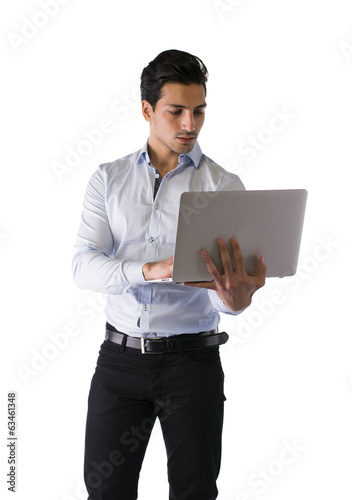 Young man standing and working on laptop computer