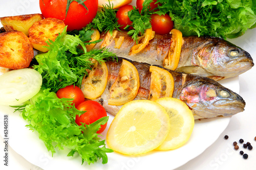 Fototapeta grilled trout with fresh herbs, vegetables and lemon