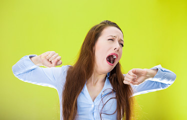 Sleepy yawning woman isolated on green background